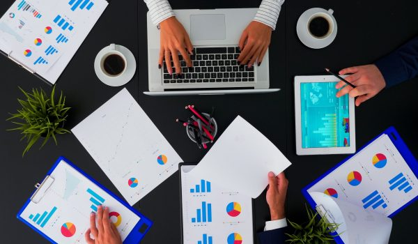 Top view of creative professional business people brainstorming innovative ideas for startup company viewing market research statistics using tablet in boardroom meeting. Copy space, flat lay concept